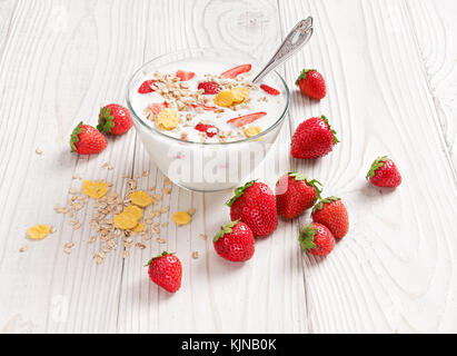 Bowl of homemade yogurt with muesli and fresh strawberry on wooden table. Fresh yogurt. Healthy food concept. High - Stock Photo
