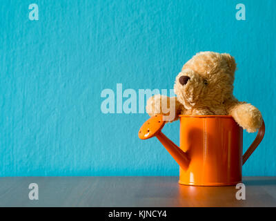 The teddy bear sitting in orange watering cans put on wooden table. the background is turquoise and copy space for - Stock Photo