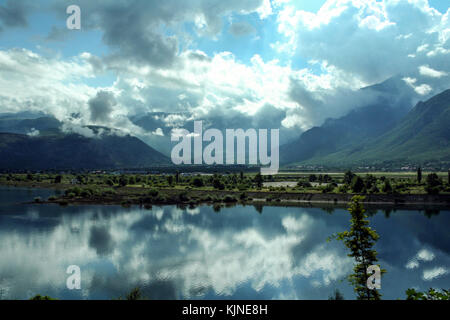 Neretva river in a valley near the city of Mostar (Bosnia and Herzegovina) with mountains and a few clouds in the - Stock Photo