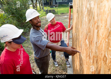 Houston, Texas - Two volunteers from Wells Fargo Bank get instruction as they help build a Habitat for Humanity - Stock Photo