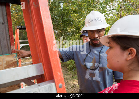 Houston, Texas - A volunteer from Wells Fargo Bank gets instruction as she helps build a Habitat for Humanity house - Stock Photo