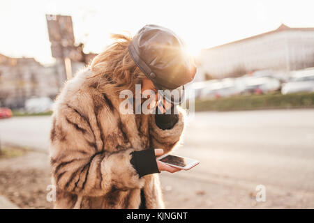 Beautiful girl smiling and texting on her cell phone on city streets - Stock Photo