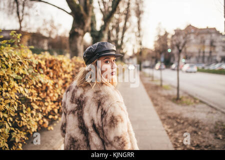 Beautiful girl wearing fur and riding her bike on the city streets - Stock Photo