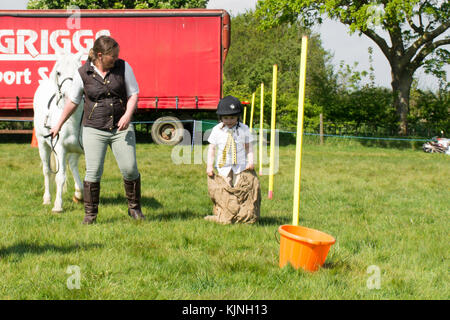girl taking part in a sack race in gymkhana games - Stock Photo