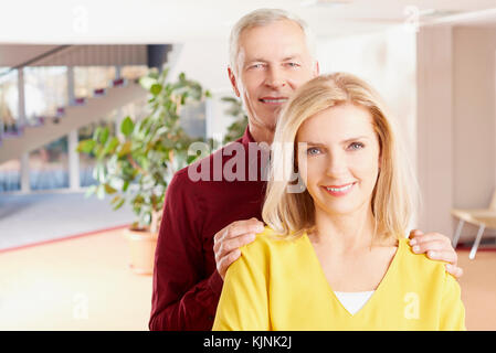 Close-up shot of an older couple embracing each other while relaxing at home. - Stock Photo