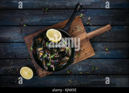 Delicious mussels. Serving on a hot frying pan with herbs spices and lemon on a colored wooden background. Top view - Stock Photo