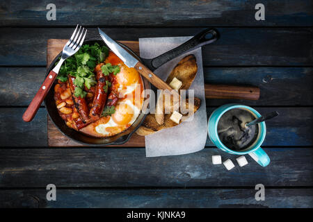 Breakfast in on a hot frying pan with fried eggs, sausages, beans, greenery and toasts. With coffee rafinated sugar - Stock Photo