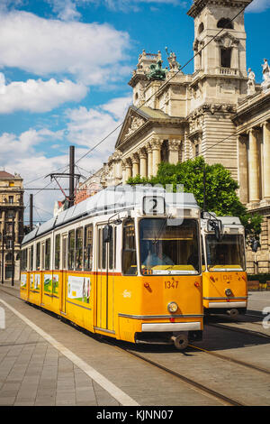 Yellow trams in front of the Museum of Ethnography in Budapest (Hungary). June 2017. Portrait format. - Stock Photo