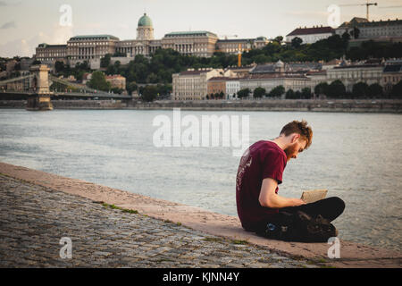 Young man sitting on the Danube river bank reading a book in Budapest (Hungary). June 2017. Landscape format. - Stock Photo
