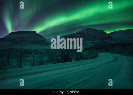 Icy road through northern Norway, under the northern lights - Stock Photo