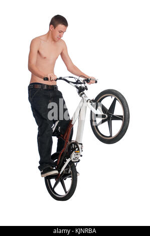 Teenage boy standing on the rear pegs of a BMX bike while performing stunts. - Stock Photo