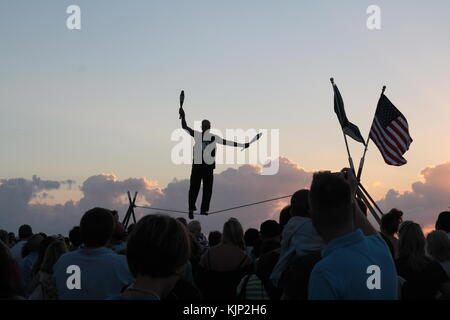 Acrobat  walking on a wire at sunset in Mallory Square, Key West, Florida. - Stock Photo