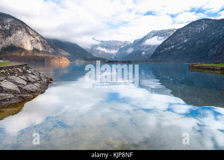 Travel destinations with the majestic Northern Limestone Alps and their reflection in the Hallstatter lake water, located in Hallstatt, Austria