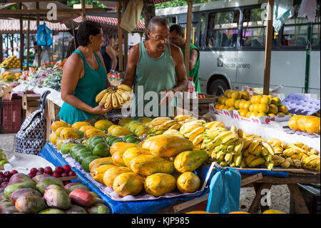 RIO DE JANEIRO - JANUARY 31, 2017: A customer buys bananas from a vendor at the weekly farmer's market in General - Stock Photo
