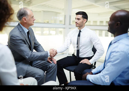 Two successful traders handshaking after discussion of contract terms - Stock Photo