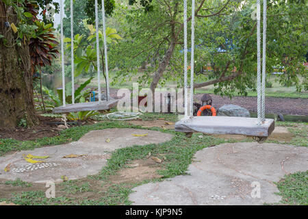 Old wooden swing two Nature seats hanging White rope in garden tree , select focus wooden swing  , Blur background - Stock Photo