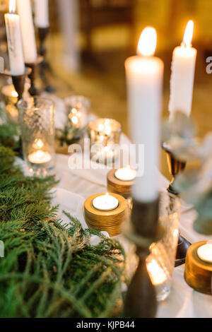 illumination, comfort, christmas feast concept. table with numerous of candles in various holders made of glass, - Stock Photo