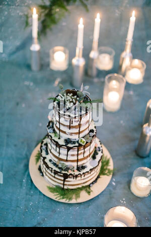 treatment, holidays, confectionary concept. gteat three tier birthday cake with leaves and flowers, with berries - Stock Photo