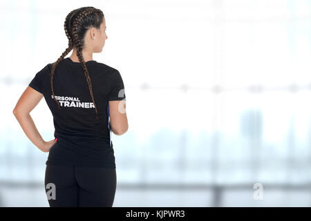 Female Personal Trainer, with his back facing the camera, in a gym - Stock Photo