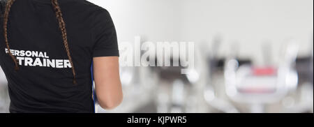 Female Personal Trainer, with his back facing the camera, looking at a gym - Stock Photo