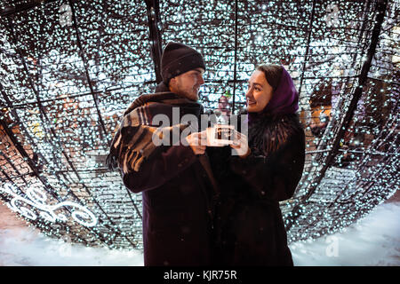 Couple celebrating Christmas with cups of hot tea near holidays decorations. Cheers! - Stock Photo