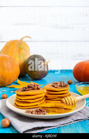 Fragrant golden pumpkin pancakes with honey and walnuts on a blue wooden background. Traditional American dish - Stock Photo