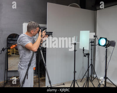 a young photographer in the process of working in a photography studio. unintended photography - Stock Photo