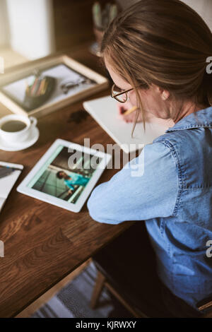 Young woman sitting alone at a table working with a digital tablet and writing down ideas on a notepad - Stock Photo