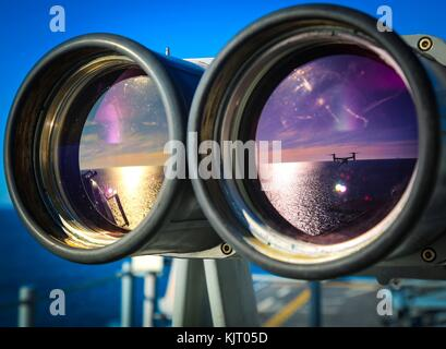 A U.S. Marine Corps MV-22B Osprey assault support aircraft is seen in the reflection of binoculars aboard the U.S. - Stock Photo