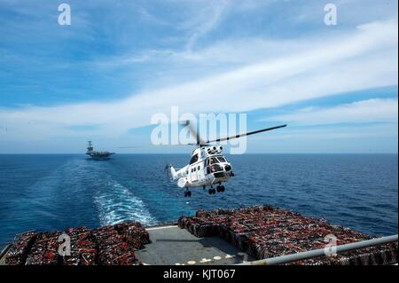 A U.S. Navy SA-330J Puma helicopter lands on the flight deck aboard the U.S. Navy Lewis and Clark-class dry cargo - Stock Photo