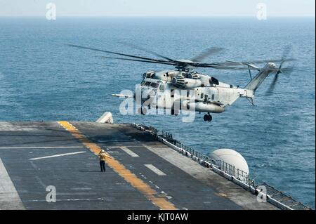 A U.S. Marine Corps CH-53E Super Stallion helicopter lands on the flight deck aboard the U.S. Navy America-class - Stock Photo