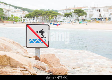 A sign indicating that jumping into the water is not allowed - Tamariu, Spain - Stock Photo