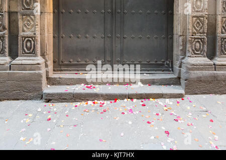 Colorful rose petal on the floor in front of an old closed church after the wedding in Barcelona, Spain - Stock Photo