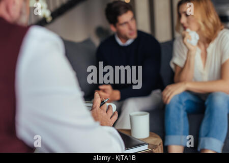 Psychologist consulting young couple in trouble. Psychotherapist taking down notes during counseling session. - Stock Photo