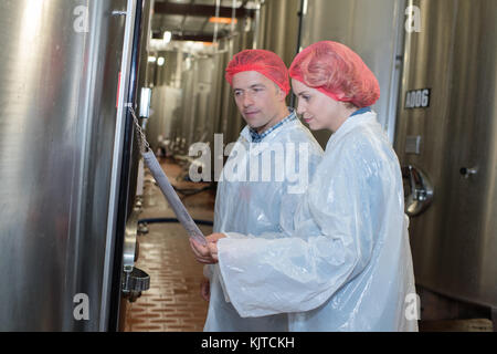 smiling farm employees working in raw milk factory - Stock Photo
