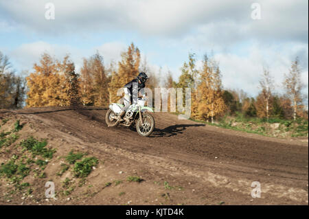 Motocross enduro rider in action accelerating the motorbike after the corner on dirt race track. Extreme off-road - Stock Photo