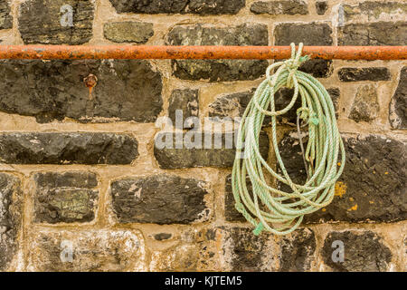 Rope hanging from a rusty rail. - Stock Photo