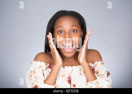 Closeup portrait of happy cute young beautiful woman taken aback in disbelief hands on face isolated gray background. - Stock Photo