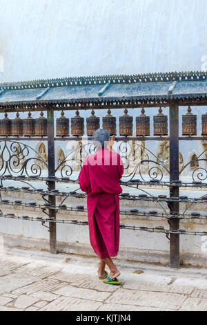 Monk turning Prayer Wheels, Swayambunath or Monkey Temple, Unesco World Heritage Site, Kathmandu, Nepal, Asia - Stock Photo