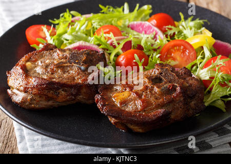 Spicy delicious lamb steak and vegetable salad from radish, tomatoes, pepper and lettuce close-up on a plate. horizontal - Stock Photo