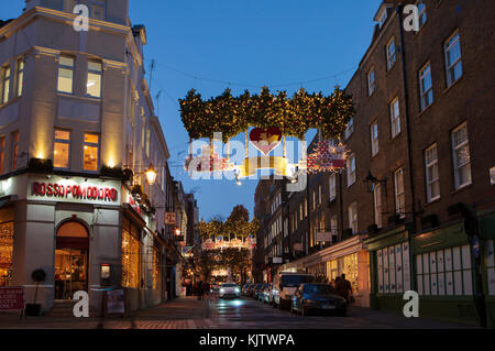 LONDON, UK - November 24th, 2017: Christmas lights on Seven Dials; seasonal lights are being displayed over busy - Stock Photo