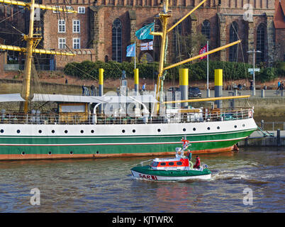 Bremen, Germany - November 23rd, 2017 - Lifeboat Flinthörn on the river Weser passing the stern of former sail training - Stock Photo