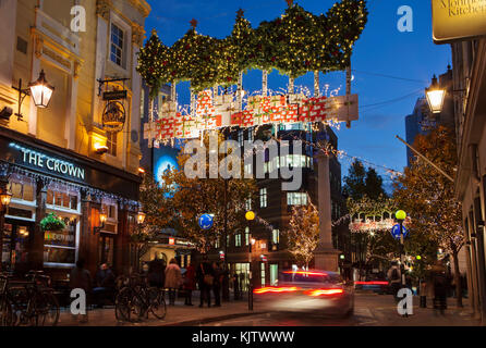 LONDON, UK - November 24th, 2017: Christmas lights on Seven Dials; seasonal lights are being displayed over busy area of central London. Stock Photo