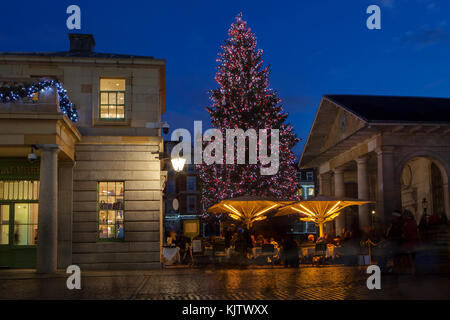 LONDON, UK - November 24th, 2017: Christmas tree in Covent Garden; seasonal lights are being displayed over famous - Stock Photo