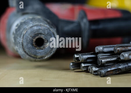 Concrete drills with sds handle. Various drill bits on the worktop. In the background the drill head. Black background. - Stock Photo