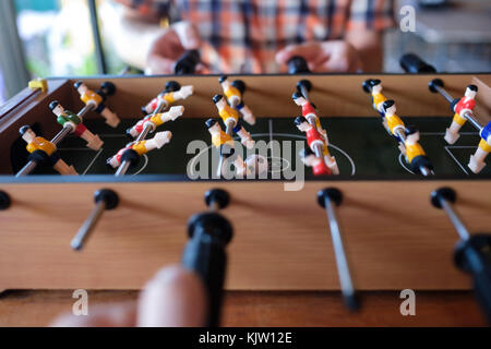 Man playing table football soccer game close up with his friends - Stock Photo