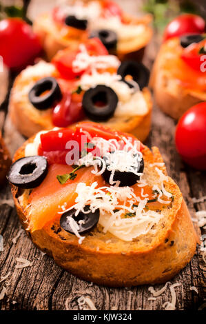 Tasty homemade bruschetta with salmon and cheese.Selective focus in the middle of bruschetta - Stock Photo