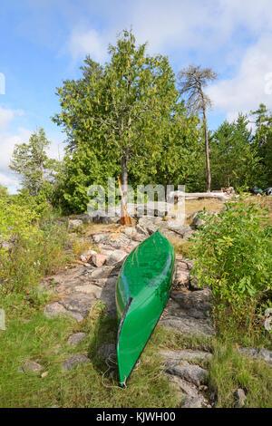 Canoe in Camp in the Shore on Kawnipi Lake in Quetico Provincial Park in Ontario - Stock Photo