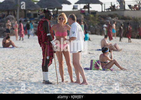 Zanzibar, Tanzania; A young Maasai warrior chats with a tourist couple by their beach hotel in the north of the - Stock Photo