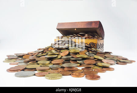 A small wooden treasure chest which is bursting with coins on a white background. Isolated composition which is - Stock Photo